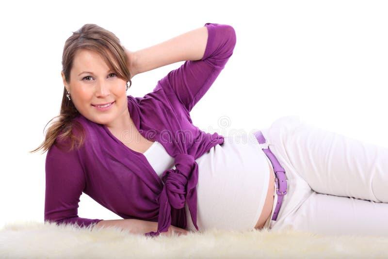 La femme enceinte se trouve sur la fourrure blanche d'isolement image libre de droits