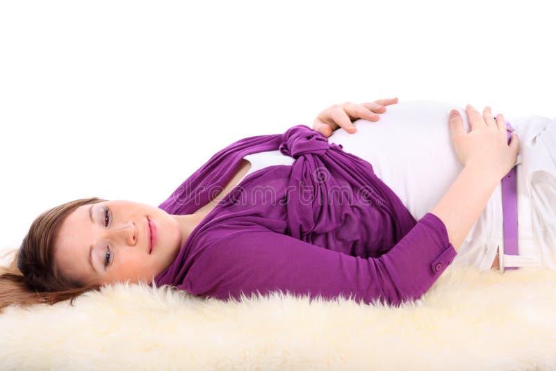 La femme enceinte se trouve sur la fourrure et touche le ventre photos libres de droits
