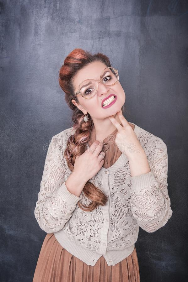 La femme ennuyée drôle tenant deux doigts s'approchent de la gorge sur le tableau photo libre de droits