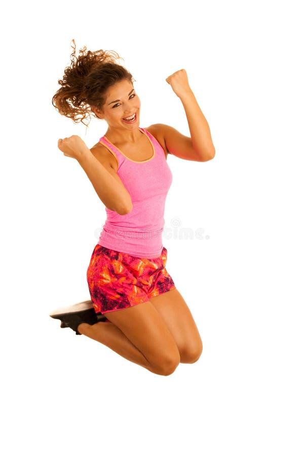 La femme enthousiaste active d'ajustement saute par-dessus le fond blanc photos libres de droits