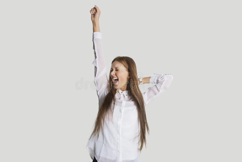 La femme enthousiaste avec le bras a soulevé des cris sur le fond blanc images stock