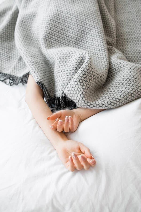 La femme entièrement couverte exceptent des mains dans le lit image libre de droits