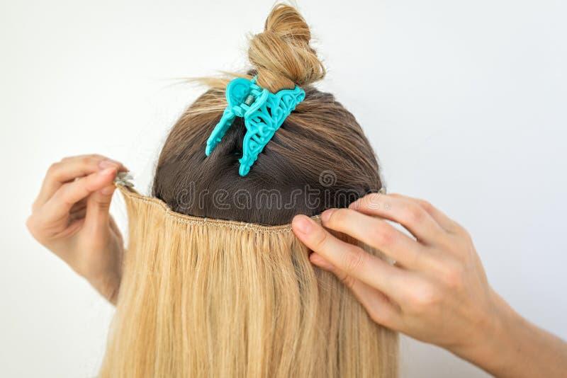 La femme essaye sur les agrafes naturelles d'extension de cheveux d'agrafe remy blonde image stock