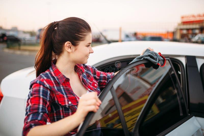 La femme essuie l'automobile, station de lavage de libre service photographie stock libre de droits