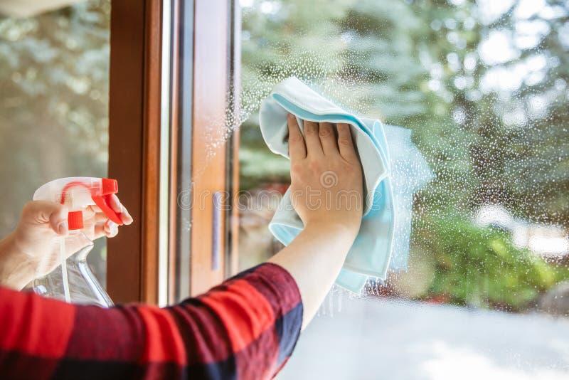 La femme essuie le liquide de nettoyage de la fenêtre image stock