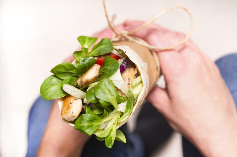 La femme est reposante et tenante l'enveloppe de tortilla avant la consommation image libre de droits