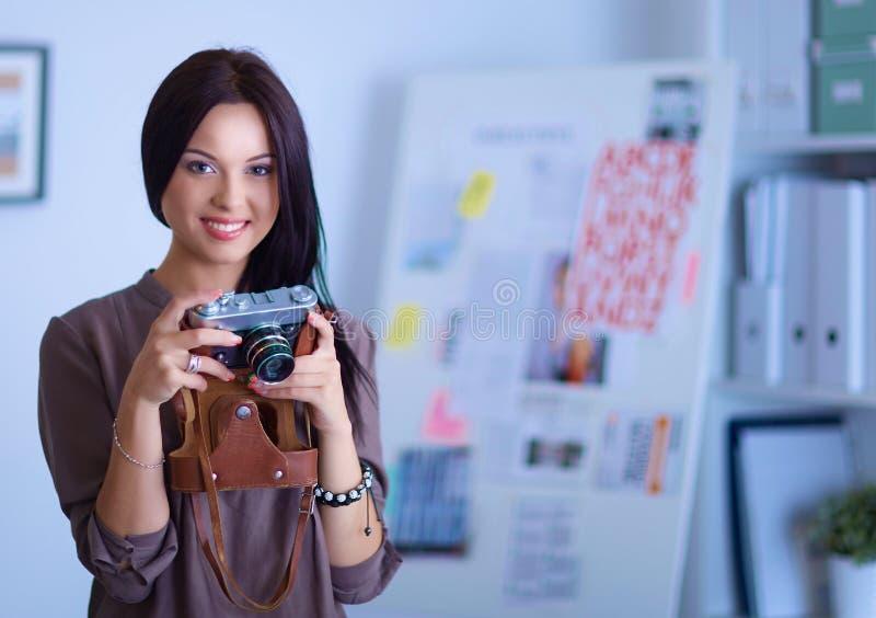 La femme est une photographe de proffessional avec l'appareil-photo photographie stock libre de droits