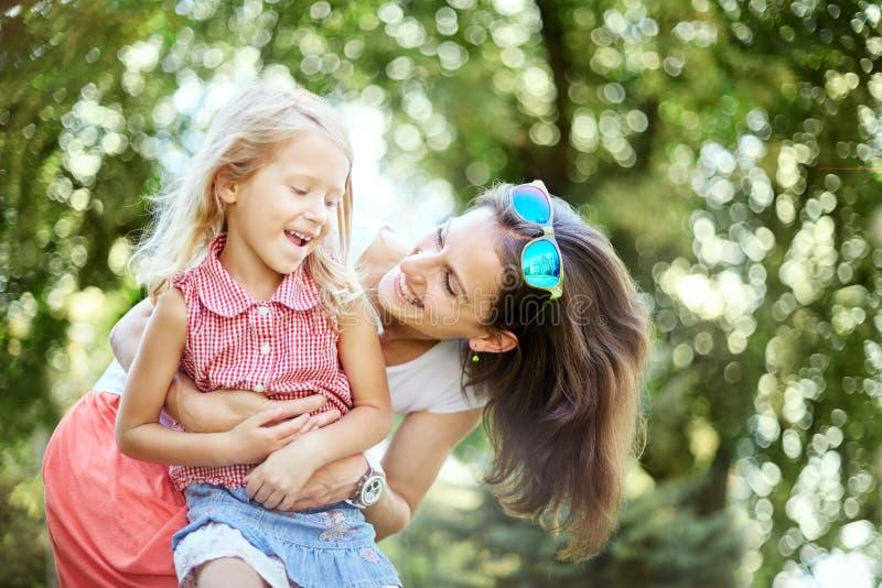 La femme et l'enfant heureux pendant le ressort de floraison font du jardinage Concept de vacances de jour de mères photo libre de droits