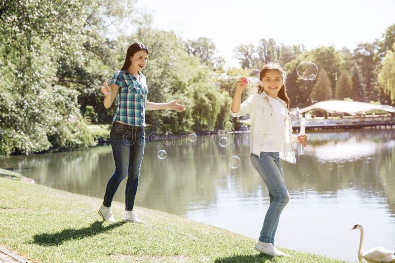 La femme et l'enfant jouent ensemble La fille souffle des bulles de savon La femme marche derrière elle et le sourire Ils sont photo stock
