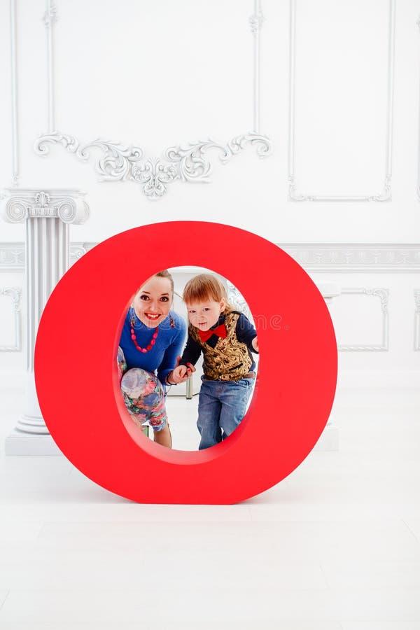 La femme et l'enfant regardent par le trou rond photographie stock