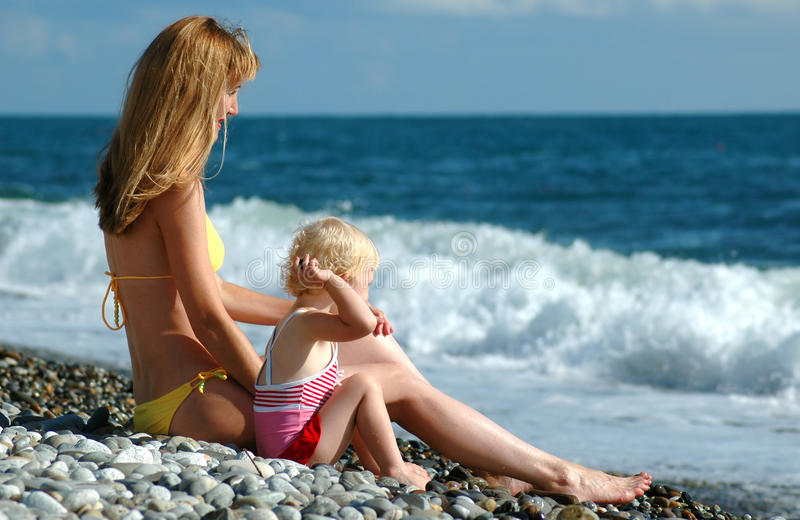 La femme et l'enfant s'asseyent sur le bord de la mer images stock