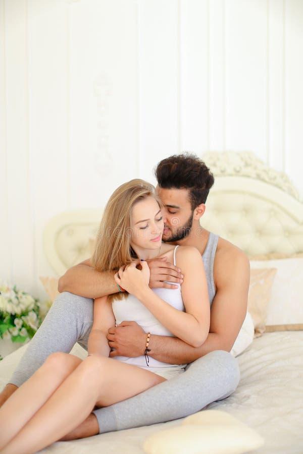 La femme et l'hispanique caucasiens blonds équipent se reposer dans le mauvais dans le matin photographie stock libre de droits