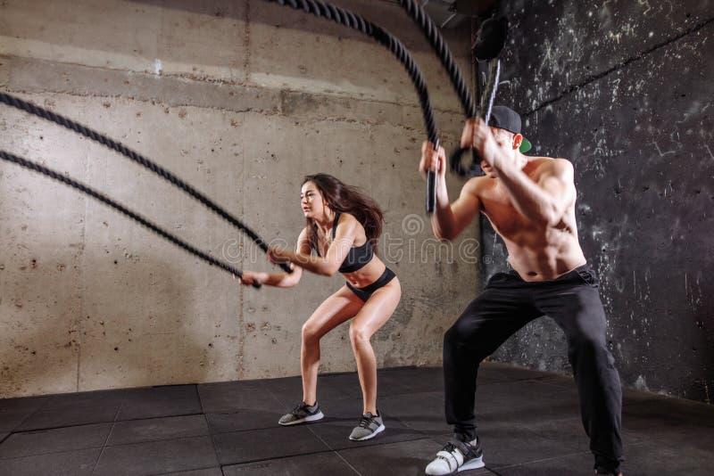 La femme et l'homme couplent former faire ensemble la séance d'entraînement de lutte de corde image stock