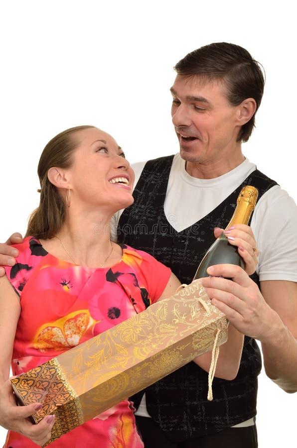 La femme et l'homme se réjouissent le cadeau du champagne cher image libre de droits