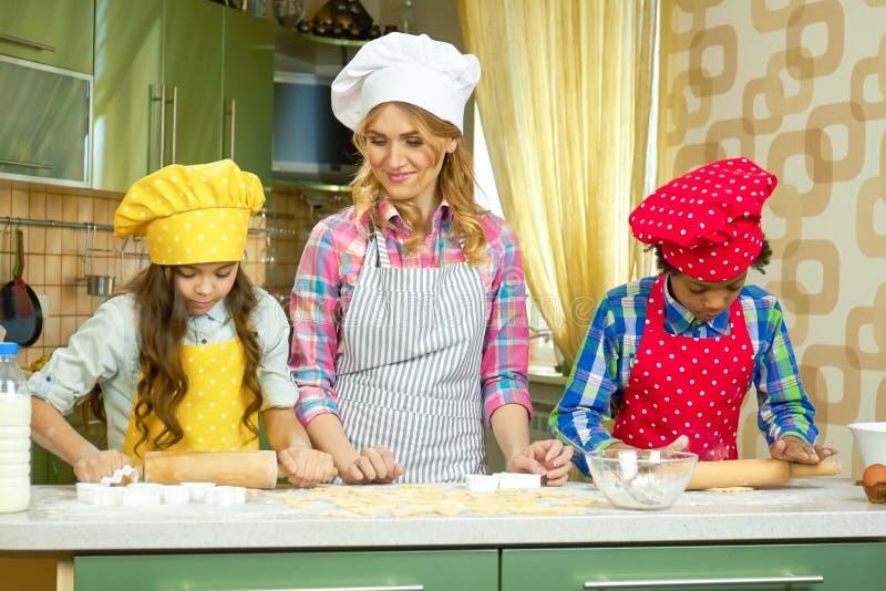 La femme et les enfants font la pâtisserie photo stock
