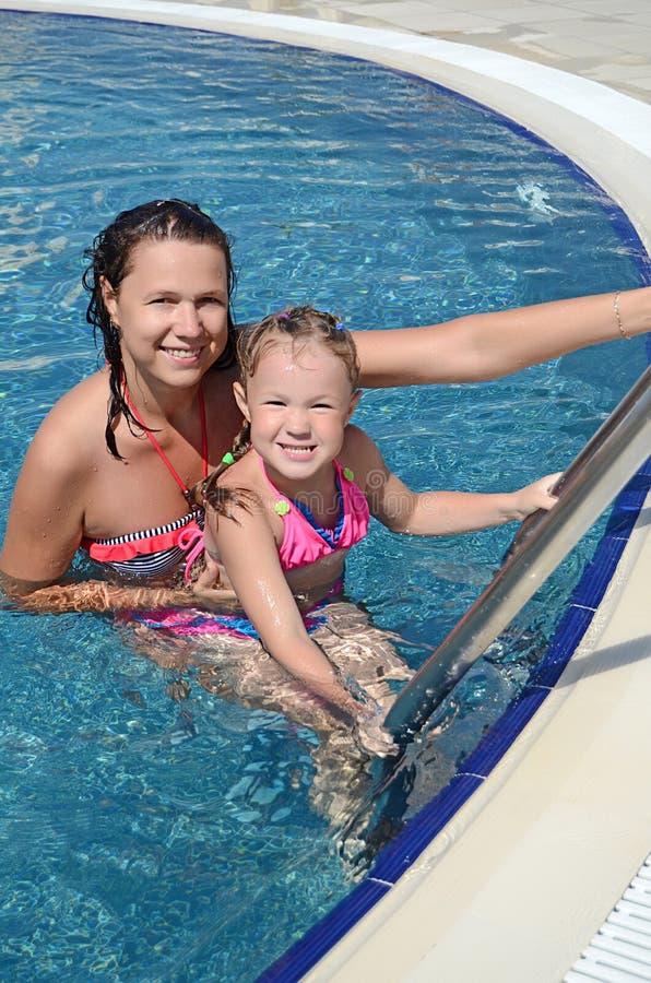La femme et sa petite fille mignonne ont un amusement dans la piscine photographie stock libre de droits
