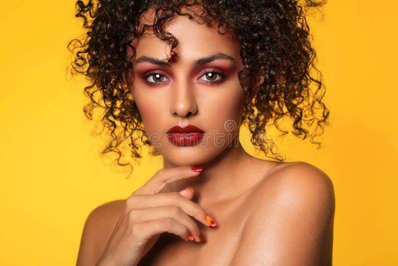 La femme ethnique avec à extrémité élevé composent image stock