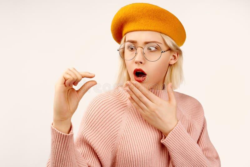 La femme européenne étonnée garde la main à la bouche, stupéfaite et appliqué, montre très minuscule ou petit petits prix dans vo photo stock