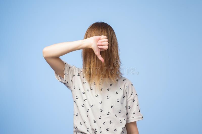 La femme européenne montre le signe de désapprobation, donne le pouce vers le bas font des gestes, détestent quelque chose, a l'e photographie stock