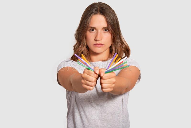 La femme européenne pleine d'assurance a l'expression du visage sérieuse, tient les pailles en plastique dans des mains, regarde  photographie stock