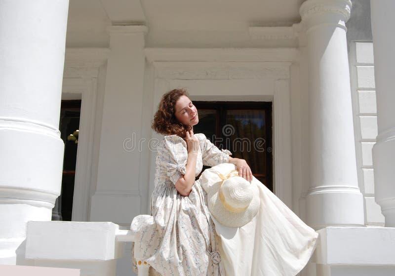 La femme européenne s'asseyant en soleil et les cheveux émouvants dans le vintage s'habillent près du palais photo stock