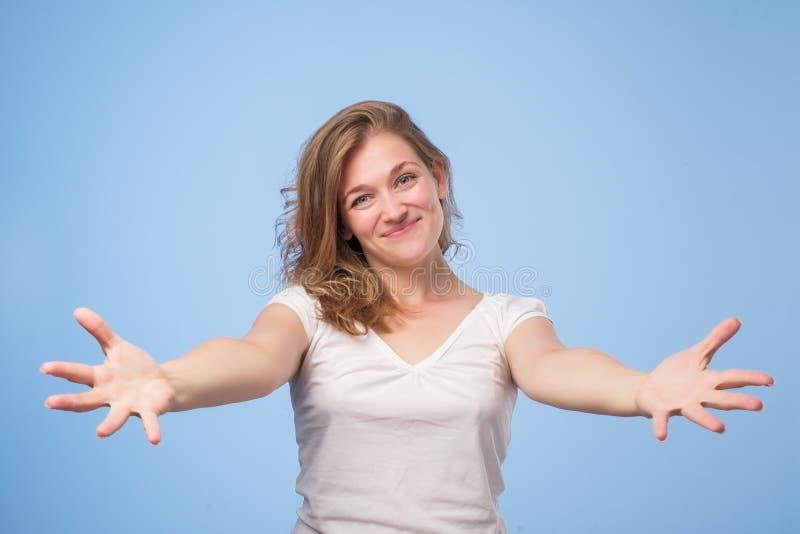La femme européenne a soulevé des mains de bras de paumes à vous, au-dessus du fond bleu photo stock