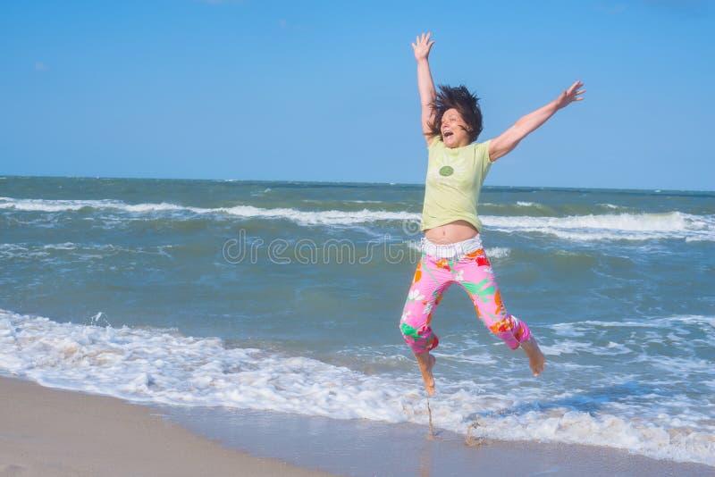 La femme expressive, avec des cheveux de vol, saute sur la plage photographie stock libre de droits