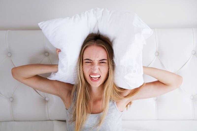 La femme fâchée agressive s'asseyant sur un lit et un screamin dans la chambre à coucher, ferment ses oreilles avec un oreiller,  photos libres de droits