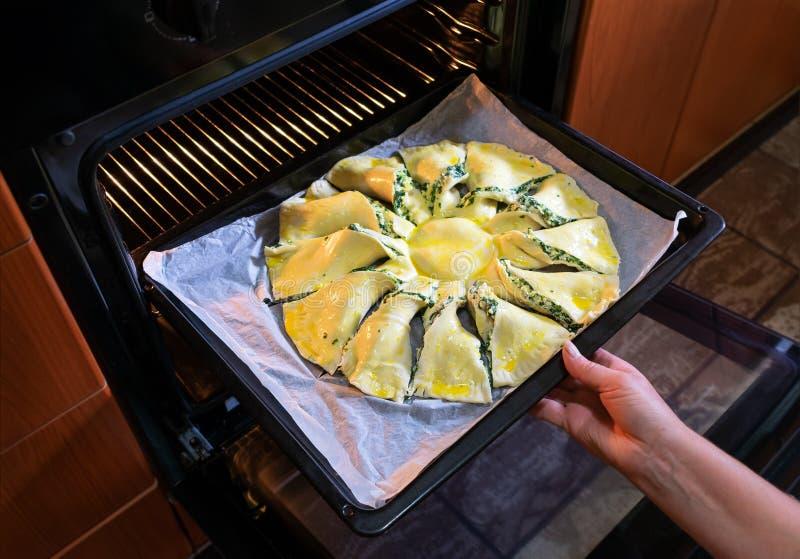 La femme faisant cuire dans la cuisine met un tarte cru dans le four Vue de plan rapproché image stock