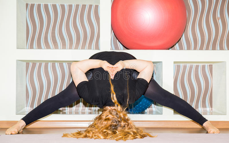 La femme faisant le yoga d'exercice et les pilates posent sur le tapis dans le gymnase Asana Le concept du sport, de la forme phy photographie stock libre de droits