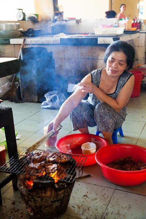 La femme fait cuire la viande sur le feu à la nourriture vietnamienne de style photographie stock