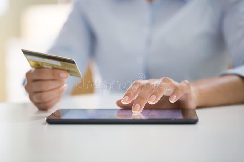 La femme fait des emplettes en ligne avec le PC de comprimé images stock