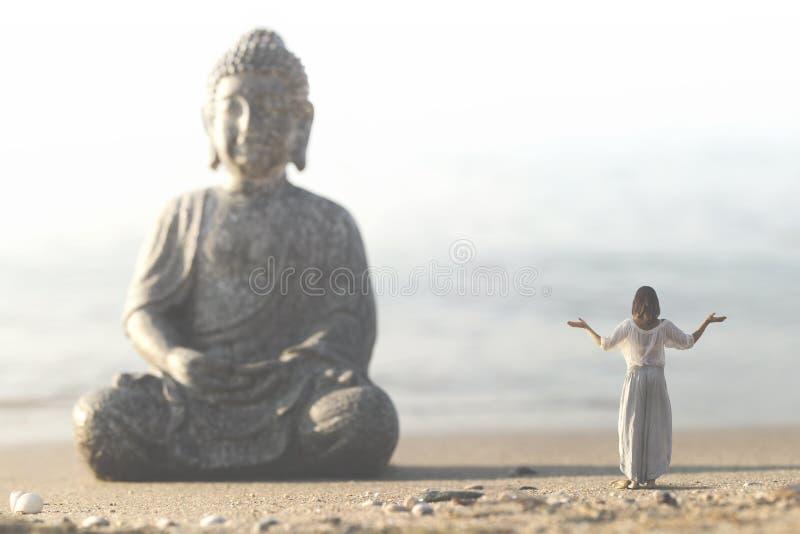 La femme fait des exercices de yoga devant la statue de Bouddha image stock