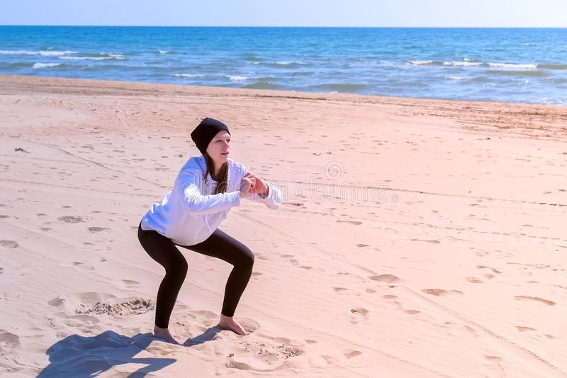 La femme fait des postures accroupies sur des exercices de sport en plein air de forme physique de plage de sable de mer sur la f photo stock