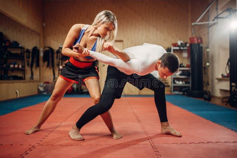 La femme fait le coup-de-pied de coude, séance d'entraînement d'autodéfense images libres de droits