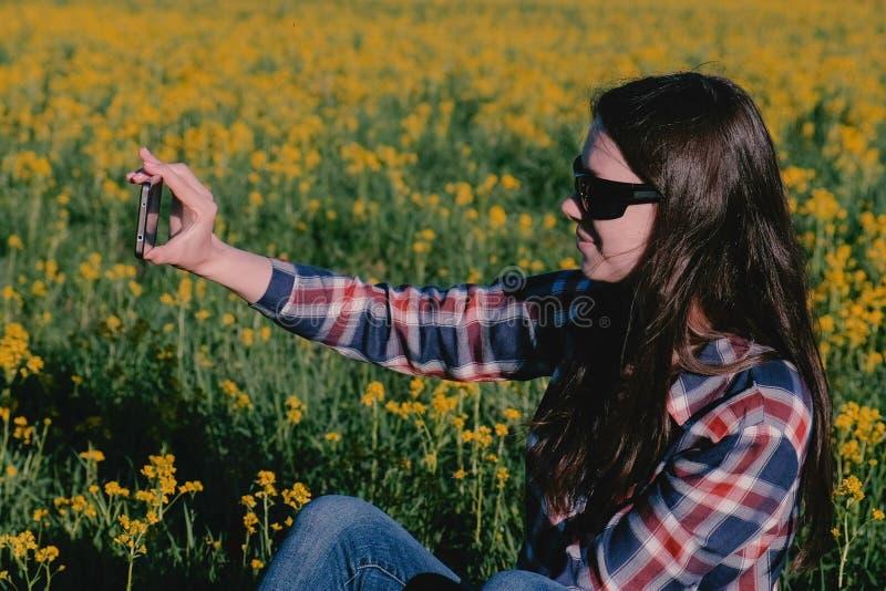 La femme fait un selfie au téléphone se reposant sur l'herbe parmi les fleurs jaunes images libres de droits
