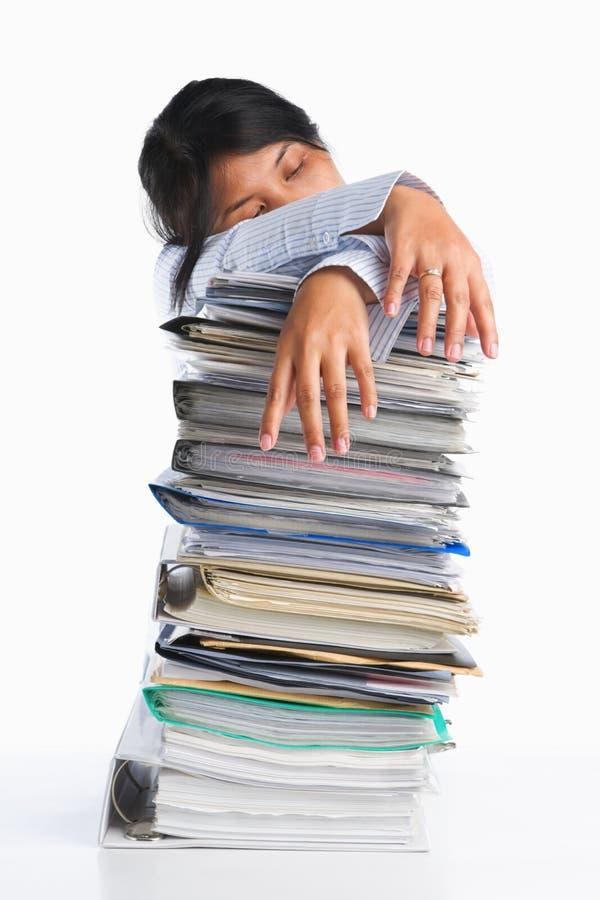 La femme a fatigué derrière la pile du papier photo stock