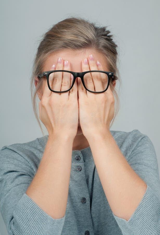La femme fatiguée dans des lunettes, couvrant le visage observe des mains image stock