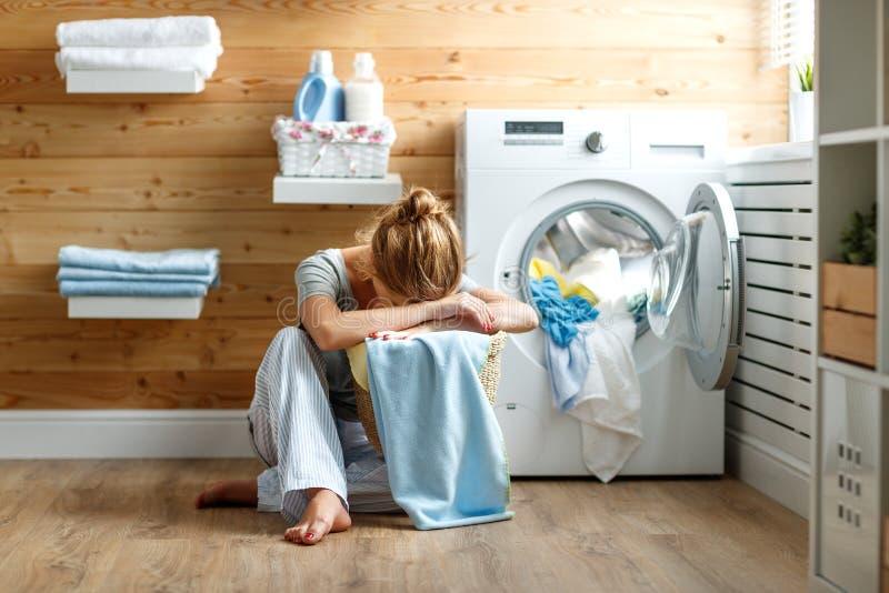 La femme fatiguée de femme au foyer dans l'effort dort dans la buanderie avec le lavage photographie stock libre de droits