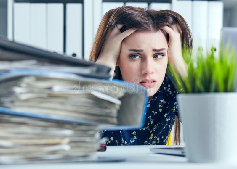 La femme fatiguée et épuisée regarde la montagne des documents étayant sa tête avec ses mains images stock