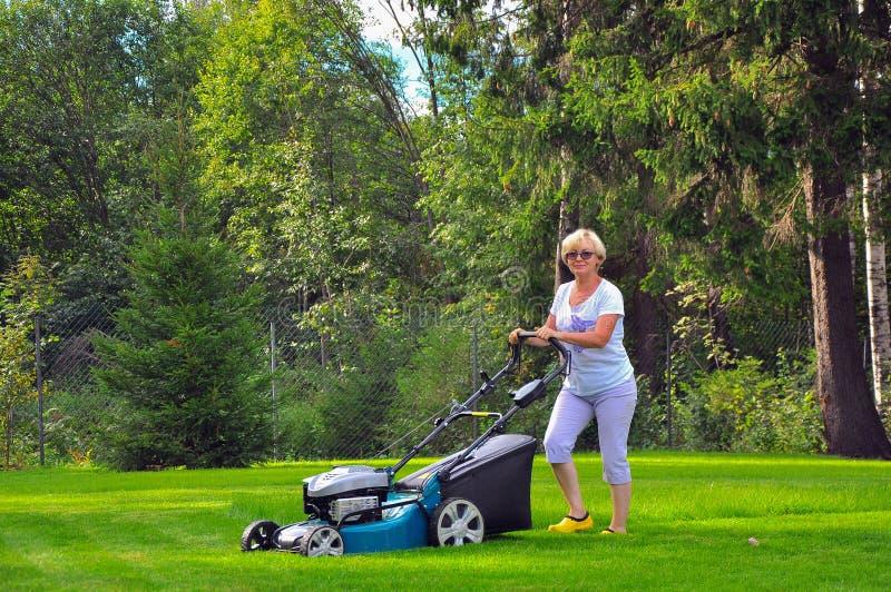 La femme fauche sa pelouse avec la tondeuse à gazon photographie stock
