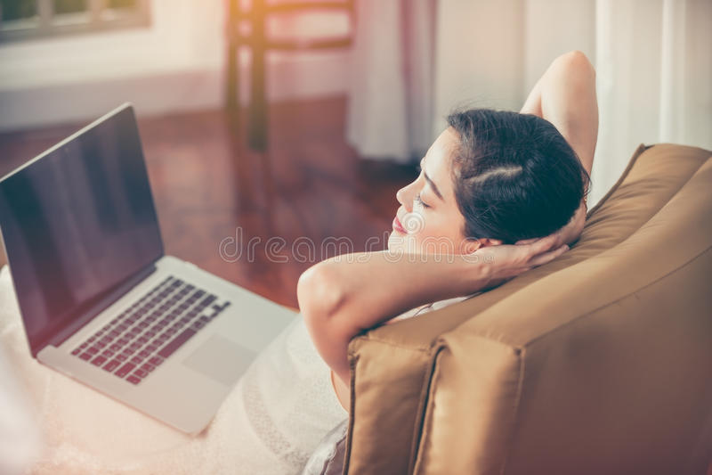 La femme a fermé des yeux et le repos après travail dur avec le compu d'ordinateur portable photo libre de droits
