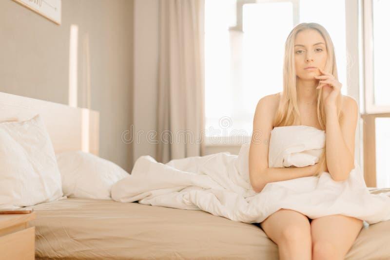 La femme ferme ses yeux se trouvant sur le lit, s'attendant à ce que son ami fasse sa surprise photos stock