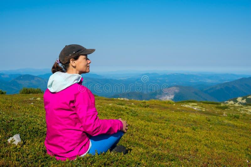 La femme fière heureuse, randonneur s'assied sur un pré vert de montagne photographie stock