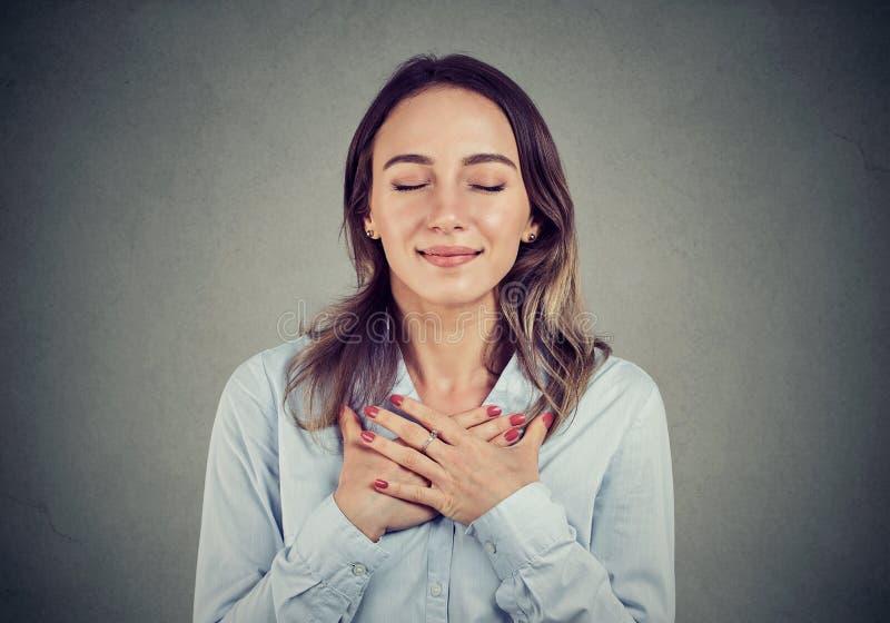 La femme fidèle avec des yeux fermés garde des mains sur le coffre près du coeur, montre la gentillesse photo libre de droits