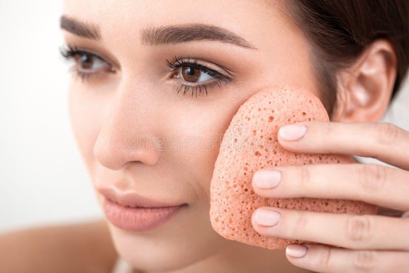 La femme font un traitement facial avec une éponge images libres de droits