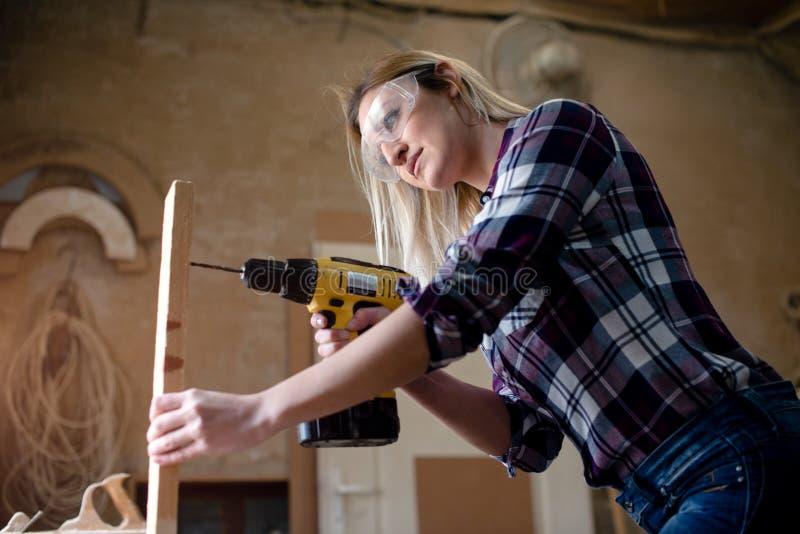 La femme fore le bois image stock