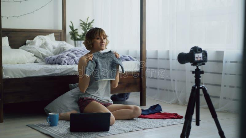 La femme gaie attirante s'asseyant près du blog visuel d'enregistrement de lit au sujet du ` s d'enfants vêtx avec l'appareil-pho image stock