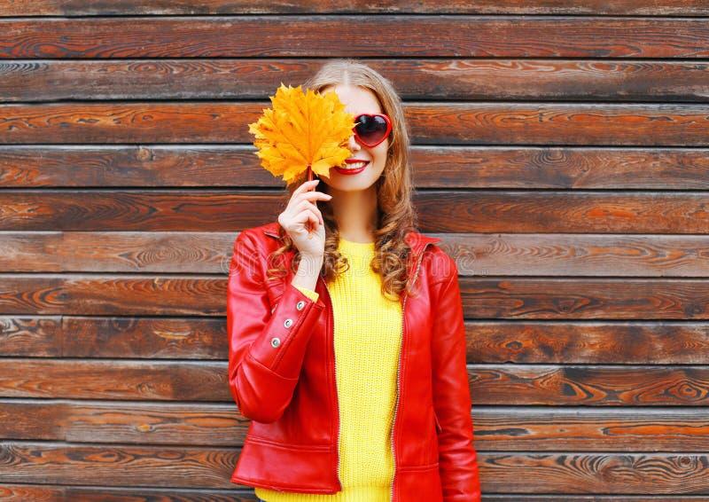 La femme gaie cache de demi feuilles d'érable de jaune d'automne de visage utilisant une veste en cuir rouge au-dessus d'en bois images libres de droits