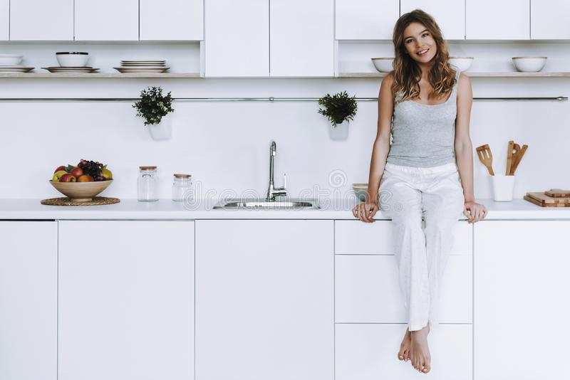 La femme gaie s'assied sur la partie supérieure du comptoir dans la cuisine moderne blanche photos libres de droits
